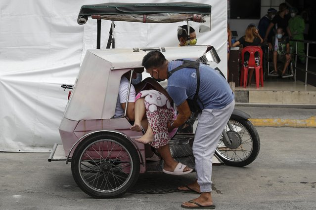 A man carries a sick woman from a pedicab as they bring her to the emergency area of the hospital that is crowded with suspected COVID-19 patients in Manila, Philippines on Monday, April 26, 2021. (Photo by Aaron Favila/AP Photo)