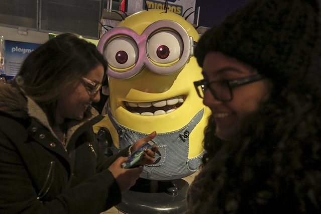 """Girls giggle after taking a photo with a Minion character inside the Toys """"R"""" Us flagship store that has closed permanently in Times Square in the Manhattan borough of New York, December 30, 2015. (Photo by Carlo Allegri/Reuters)"""