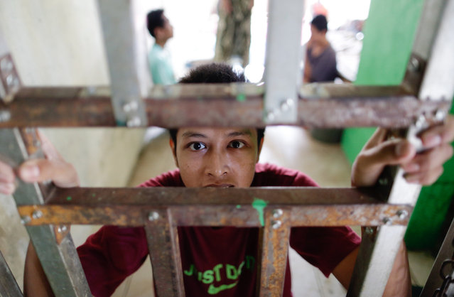 A psychiatric patient, Agus, stands behind bars at Daarul Miftah Mulia foundation in Bogor, Indonesia, 08 April 2021. The Daarul Miftah Mulia foundation accommodates people with mental illness including patients who suffers from depression due to COVID-19 pandemic. (Photo by Adi Weda/EPA/EFE)
