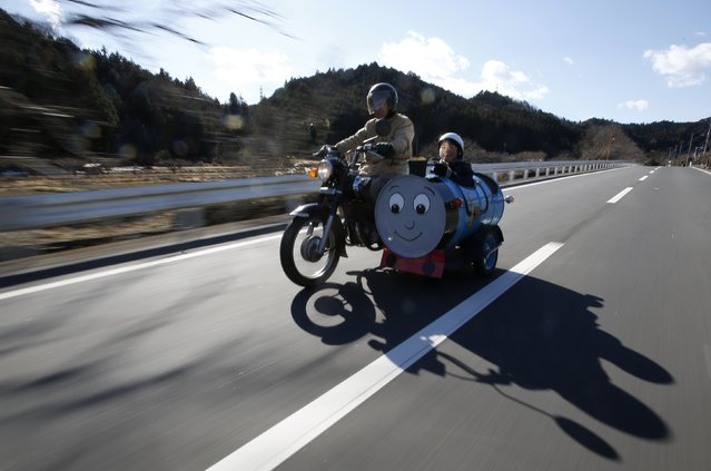 Sadao Kimbara (L) rides on a Honda motorcycle with a sidecar he made out of an oil barrel as his grandson Rui smiles in the sidecar in Ome, outskirts of Tokyo February 14, 2015. Saudi Arabia's oil exports have risen in February in response to stronger demand from customers. As OPEC's top producer battles for market share Reuters photographers around the globe have been photographing oil barrels to document how they are utilised once the fuel has been used. (Photo by Toru Hanai/Reuters)