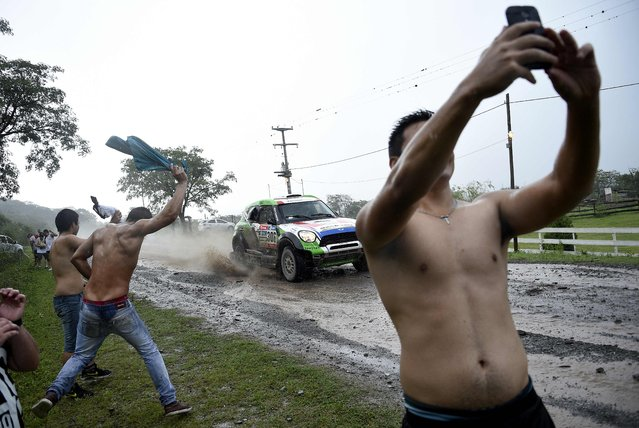 Spectators cheer and take selfies as driver Erik Van Loon and co-driver Wouter Rosegaar, both from the Netherlands, compete in the Stage 3 of the 2016 Dakar Rally between Termas de Rio Hondo and Jujuy, Argentina, on January 5, 2016. (Photo by Franck Fife/AFP Photo)