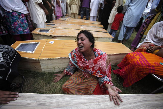 A Christian woman mourns next to the coffin of her brother, who was killed in a suicide attack on a church, in Peshawar September 22, 2013. A pair of suicide bombers blew themselves up outside a 130-year-old church in Pakistan after Sunday Mass, killing at least 56 people in the deadliest attack on Christians in the predominantly Muslim South Asian country. (Photo by Fayaz Aziz/Reuters)