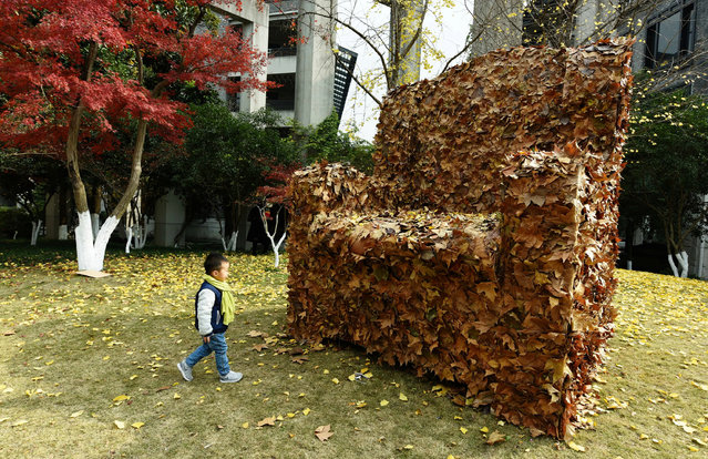 A child walks to an installation made from fallen leaves by college students, in shape of a sofa, to call for people's attention to environment protection, in Hangzhou, Zhejiang province, China, December 6, 2016. (Photo by Reuters/China Daily)