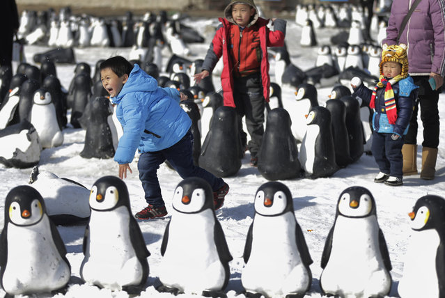 Children play in the snow near penguin sculptures installed at Taoranting Park's temple fair for Lunar New Year celebrations in Beijing Monday, February 23, 2015. Chinese spend a week-long holiday, flocking to public parks' temple fairs to celebrate the Lunar New Year, the Year of the Sheep which started on Feb. 19. (Photo by Andy Wong/AP Photo)