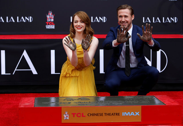 Actors Emma Stone and Ryan Gosling show their hands after placing them in cement during a ceremony in the forecourt of the TCL Chinese theatre in Hollywood, California U.S., December 7, 2016. (Photo by Mario Anzuoni/Reuters)