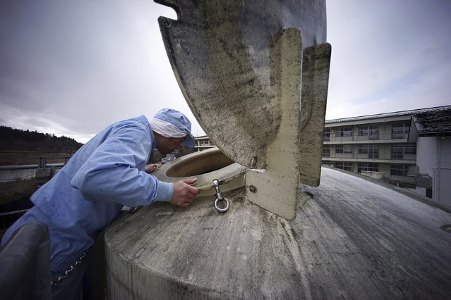 "In this Friday, March 6, 2015 photo, a worker of Yagisawa Shoten Co., checks a soy sauce tank of the company's new factory in Ichinoseki, Iwate Prefecture, northeastern Japan. The traditional soy-sauce maker, destroyed by a giant tsunami four years ago, has made a comeback, defying tsunami-scale odds. The secret lies in a little white bottle, named ""the miracle,"" which holds the special ingredients that were passed down for decades. (AP Photo/Eugene Hoshiko)"