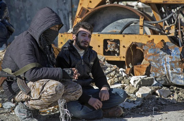 A Syrian man cries during an evacuation operation of rebel fighters and their families  from rebel-held neighbourhoods on December 15, 2016 in the embattled city of Aleppo. A convoy of ambulances and buses left rebel territory in Aleppo in the first evacuations under a deal for opposition fighters to leave the city after years of fighting. The rebel withdrawal will pave the way for President Bashar al-Assad's forces to reclaim complete control of Syria's second city, handing the regime its biggest victory in more than five years of civil war. (Photo by Karam Al-Masri/AFP Photo)