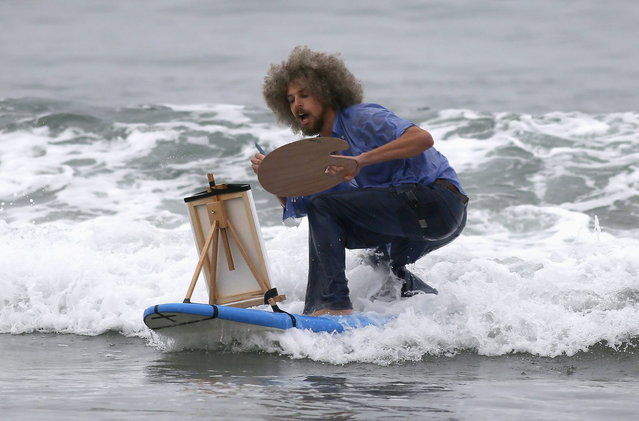 David Nickerson, 28, competes dressed as artist Bob Ross, during the ZJ Boarding House Halloween Surf Contest in Santa Monica, California October 26, 2013. (Photo by Lucy Nicholson/Reuters)