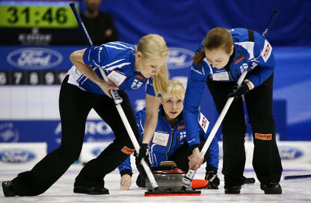 Finland's skip Sanna Puustinen (C) delivers a stone as her team mates Oona Kauste (L) and Marjo Hippi sweep during their curling round robin game against Canada at the World Women's Curling Championships in Sapporo March 14, 2015. (Photo by Thomas Peter/Reuters)