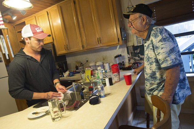 Jagger Colarossi (L) of Chicago washes dishes and talks with condo owner Howard Jones while he inspects the condo before the group leaves spring break in Panama City Beach, Florida March 13, 2015. The Jones' rented their condo out to Colarossi and his friends and said they have had no problems with the students. (Photo by Michael Spooneybarger/Reuters)