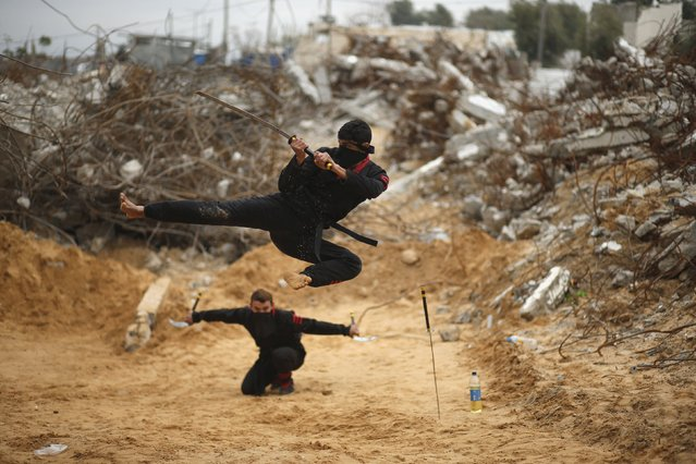 A Palestinian youth jumps with a sword as he demonstrates his ninja-style skills for the photographer in front of the ruins of buildings, that were destroyed in 2014 war, in the northern Gaza Strip January 29, 2016. The youths, who have been receiving martial arts training at local clubs in Gaza for the past two years, decided to form a team to hold regular shows in the hope that the publicity generated will eventually lead to them being invited to participate in international contests. (Photo by Mohammed Salem/Reuters)