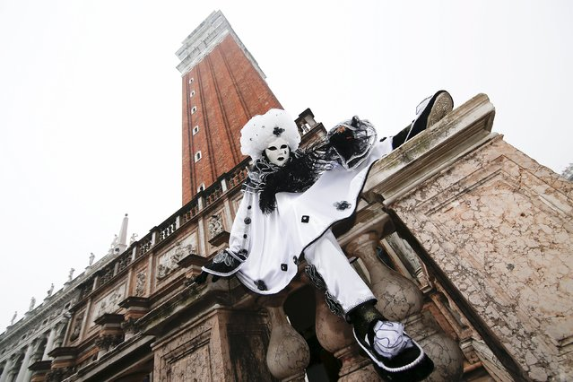 A masked reveller (R) poses in San Marco Piazza during the Venice Carnival, January 30, 2016. (Photo by Alessandro Bianchi/Reuters)