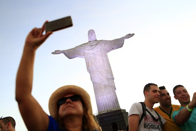 A woman poses for a selfie in front of the statue of Christ the Redeemer ahead of the 2014 World Cup in Rio de Janeiro, in this June 8, 2014 file photo. (Photo by Tony Gentile/Reuters)