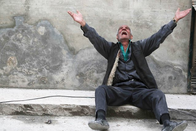 A man reacts at a site hit by what activists say was a barrel bomb dropped by forces loyal to Syria's President Bashar al-Assad, in Aleppo's al-Fardous district April 29, 2015. (Photo by Hosam Katan/Reuters)