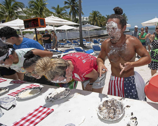 In this photo provided by the Florida Keys News Bureau, Nicholas Luera, right, points to an empty pie pan after winning the World Key Lime Pie Eating Championship Sunday, July 4, 2021, in Key West, Fla. Luera, a Seattle resident, consumed a 9-inch pie in two minutes, 13.5 seconds. The eating competition has become a July 4th tradition in the Florida Keys and is the island chain's answer to New York City's hotdog-eating contest. The contest and other July 4th events are occurring despite a tropical storm warning in place for most of the Keys because of Tropical Storm Elsa. Weather forecasters say that Elsa's tropical storm-force winds are not likely to begin affecting the Keys until late Monday afternoon. Officials are not planning visitor or resident evacuations. (Photo by Rob O'Neal/Florida Keys News Bureau via AP Photo)