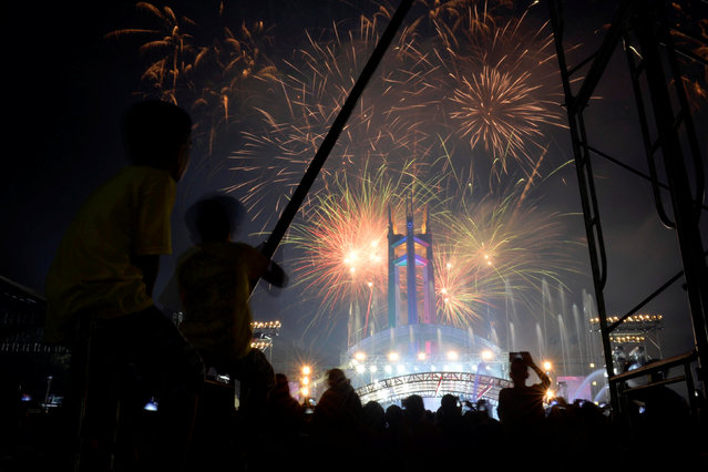 Revellers watch as fireworks explode over the Quezon Memorial Circle during New Year's celebrations in Quezon City, Metro Manila, Philippines January 1, 2017. (Photo by Ezra Acayan/Reuters)