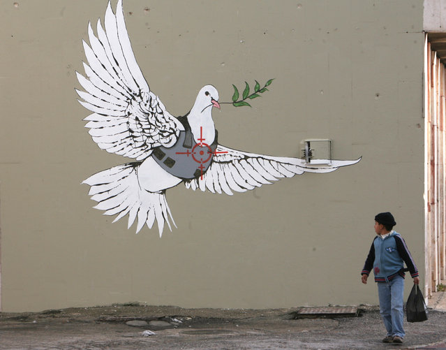A Palestinian boy looks at an image painted by Banksy as part of a Christmas exhibition in the West Bank town of Bethlehem in 2007. (Photo by Ammar Awad/Reuters)