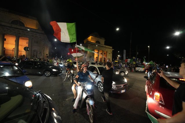 Italy's fans celebrate in Milan, Italy, Monday, July 12, 2021, after Italy beat England to win the Euro 2020 soccer championships in a final played at Wembley stadium in London. (Photo by Luca Bruno/AP Photo)