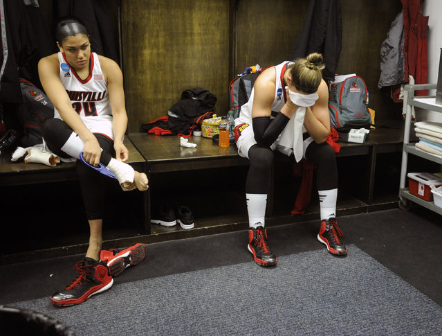 Louisville players Ariana Freeman, left, and Sara Hammond sit in the locker room folloring their 82-66 loss to Dayton in a women's college basketball regional semifinal game in the NCAA Tournament on Saturday, March 28, 2015, in Albany, N.Y. (Photo by Tim Roske/AP Photo)