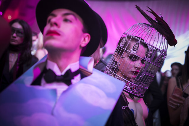 "Masked guests attend the ""Grand Bal Christian Dior"" during the Haute Couture Spring-Summer 2018 fashion collection presented in Paris, Monday, January 22, 2018. (Photo by Kamil Zihnioglu/AP Photo)"