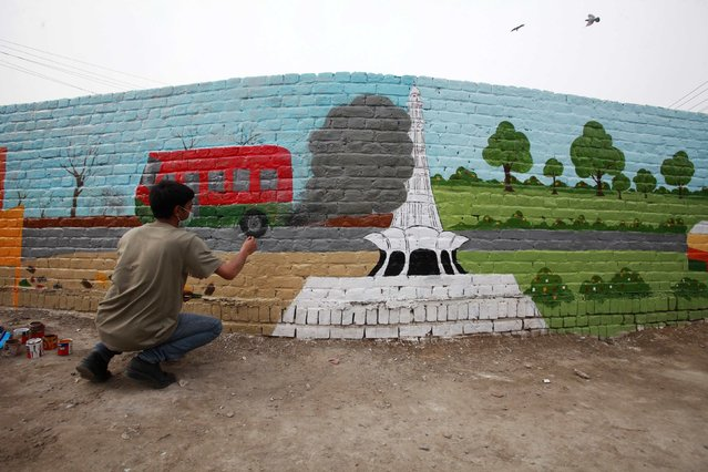 An arts student paints a mural on a wall in Lahore, February 16, 2015. (Photo by Mohsin Raza/Reuters)