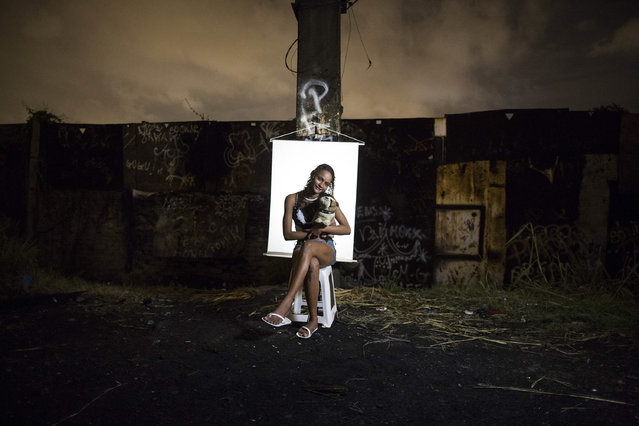 "In this March 18, 2015 photo, Ketellin Silva 17, poses for a portrait in an open-air crack cocaine market, known as a ""cracolandia"" or crackland, where users can buy crack, and smoke it in plain sight, day or night, in Rio de Janeiro, Brazil. Silva, the mother of a 3-year-old girl, holds a stuffed toy dog she says belongs to her premature infant son who remains hospitalized. (Photo by Felipe Dana/AP Photo)"