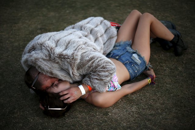 A couple lies on the grass before Kaskade plays at the Coachella Valley Music and Arts Festival in Indio, California April 12, 2015. (Photo by Lucy Nicholson/Reuters)