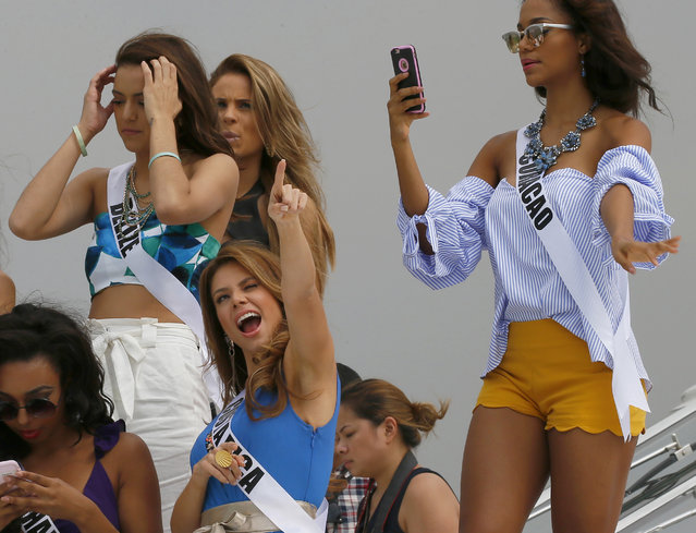Miss Universe contestant Carolina Duran of Costa Rica, center, reacts to a TV network's drone as others prepare to pose from the deck of the yacht Happy Life prior to cruising to a beach resort in Batangas province Thursday, January 19, 2017 at the Philippine Navy headquarters in Manila, Philippines. Eighty-six candidates from around the world are vying for the title to succeed Pia Wurtzbach from the Philippines. The competition takes place on Jan. 30. They are, from left, Cherell Williamson of Bahamas, Rebecca Rath of Belize, Hildur Maria of Iceland, and Chanelle de Lau of Curacao. (Photo by Bullit Marquez/AP Photo)