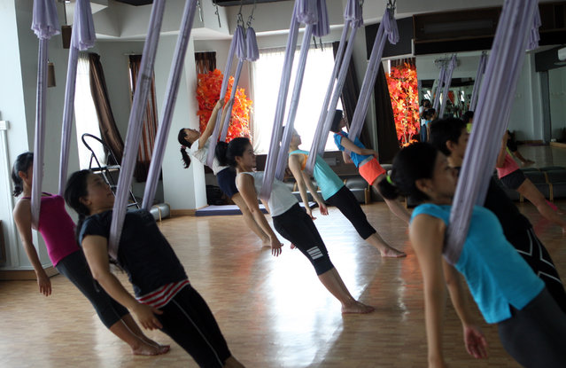"Some women stretching using hammocks as they attend the Anti-Gravity yoga class at Svarga e-Motion Sanctuary at Dharmawangsa Square, Jakarta, Saturday, April 18, 2015. Anti-Gravity Yoga or ""aerial yoga"", is a new type of yoga, originating in New York but now being practised in several countries, which combines the traditional yoga poses, pilates and dance with the use of a hammock. (Photo by Jurnasyanto Sukarno/JG Photo)"