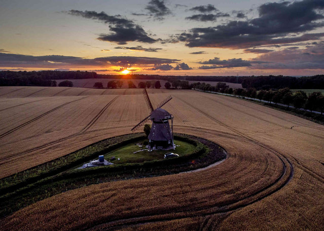 The sun sets behind a windmill on a field in Farve at the Baltic Sea,Germany, late Monday, August 2, 2021. (Photo by Michael Probst/AP Photo)