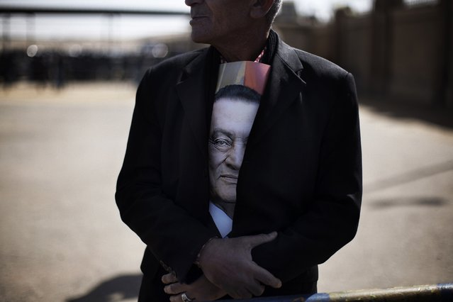 A supporter of ousted Egyptian president Hosni Mubarak (portrait) waits for news from his trial outside the court in Cairo on February 22, 2012, as the landmark murder and corruption trial of the former leader entered its final day of hearings, with the judge expected to announce the date of the verdict. (Photo by Marco Longari/AFP Photo)