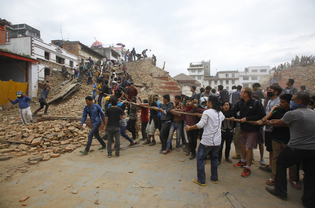 Volunteers help remove debris of a building that collapsed at Durbar Square, after an earthquake in Kathmandu, Nepal, Saturday, April 25, 2015. (Photo by Niranjan Shrestha/AP Photo)