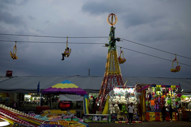 In this March 18, 2015 photo, people ride in a swing over the Texcoco Fair on the outskirts of Mexico City. Now in its 34th year, the International Horse Fair, more commonly known as the Texcoco Fair, is among the most popular gatherings of its kind in the country. (Photo by Eduardo Verdugo/AP Photo)