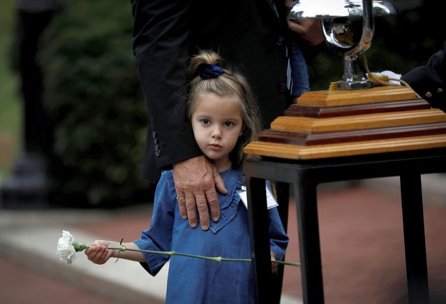 Four-year-old Elliana Barresi, the daughter of late New York City Fire Department (FDNY) officer Carmine J. Barresi, holds a flower at the annual FDNY memorial service for members who died in 2021, at the Fireman's Memorial on Manhattan's upper west side in New York City, New York, U.S., October 6, 2021. (Photo by Mike Segar/Reuters)