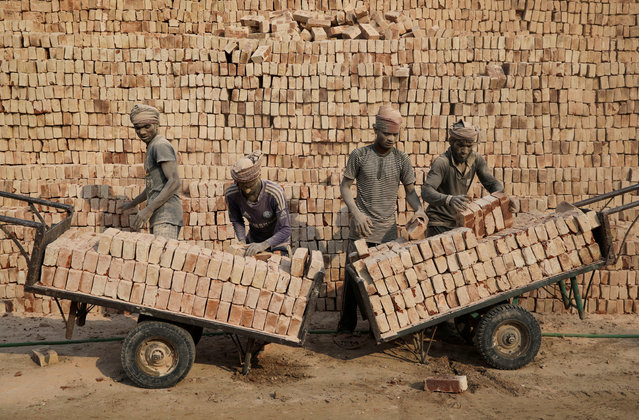 A brick factory workers stack bricks on carts in Dhaka, Bangladesh, January 9, 2019. (Photo by Mohammad Ponir Hossain/Reuters)