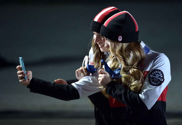 Gold medallist Justine Dufour-Lapointe (R) of Canada and silver medalist Chloe Dufour-Lapointe (R) of Canada take pictures of themselves after the medal ceremony for the Freestyle Skiing Women's Moguls at the Sochi 2014 Olympic Games, Sochi, Russia, 09 February 2014. (Photo by Hannibal Hanschke/EPA)