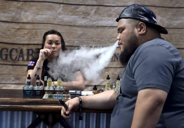 """Annie Young (L) and Dan Leano smoke e-cigs at the Vape Summit 3 in Las Vegas, Nevada May 2, 2015. According to new research provided to Reuters, youngsters say that the flavors of the vaping liquids, and the """"ability to do tricks"""" are the top two reasons they consider electronic vaping devices cool. (Photo by David Becker/Reuters)"""