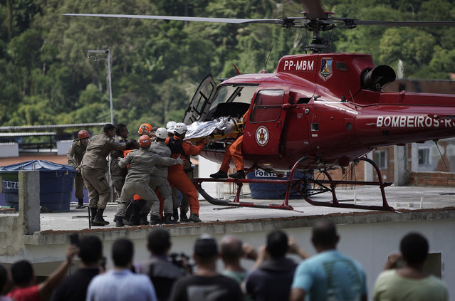 Firefighters place an injured person into a helicopter who was rescued from the rubble of two buildings that collapsed in the Muzema neighborhood, in Rio de Janeiro, Brazil, Friday, April 12, 2019. The collapse came in a western part of the city that was particularly hard hit by heavy rains this week that caused massive flooding. (Photo by Leo Correa/AP Photo)