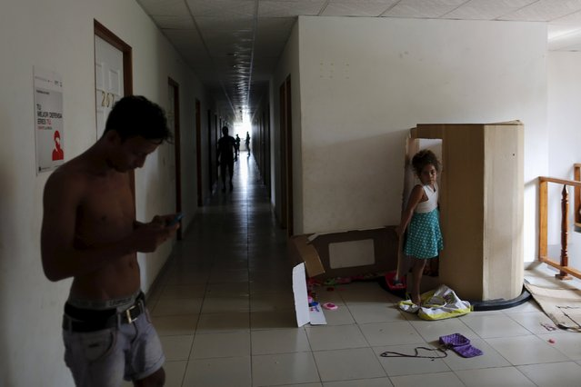 A child plays in a doll house made from a carton, inside an old hotel used as a provisional shelter in Paso Conoa, at the border with Costa Rica March 20, 2016. (Photo by Carlos Jasso/Reuters)