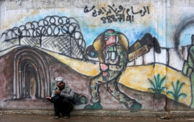 A Palestinian man begs for money as he sits in front of a mural at a street in Khan Younis in the southern Gaza Strip March 28, 2016. (Photo by Ibraheem Abu Mustafa/Reuters)