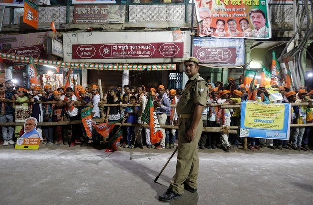 Supporters of India's Prime Minister Narendra Modi wait for his arrival as a policeman stands guard during a roadshow in Varanasi, India, April 25, 2019. (Photo by Adnan Abidi/Reuters)