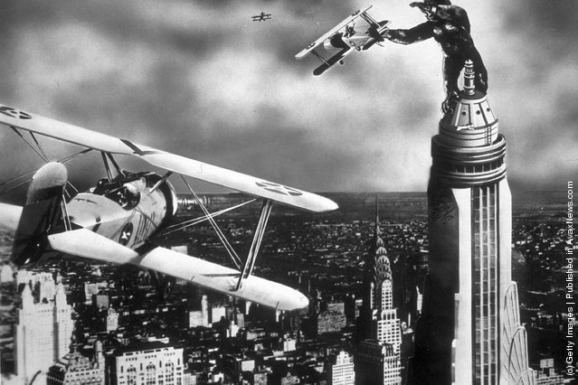 A scene from the film King Kong with the giant gorilla astride a Manhattan skyscraper grabbing a passing aeroplane