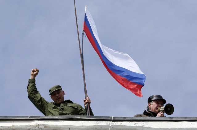A man holds a Russian flag on the roof of the Ukrainian naval headquarters in Sevastopol, Crimea, March 19, 2014. Three Russian flags were flying at one of the entrances to Ukraine's naval headquarters in the Crimean port of Sevastopol on Wednesday, suggesting that at least some of the base was under the control of pro-Russian forces. (Photo by Vasily Fedosenko/Reuters)