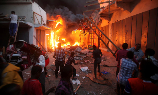 Somali traders attempt to salvage some of their wares from the burning stalls at the main Bakara market in Somalia's capital Mogadishu, February 27, 2017. (Photo by Ismail Taxta/Reuters)
