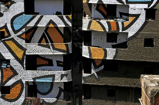 """Bags of garbage are left on a balcony of a building, which makes up part of a mural painted on the walls of houses in Zaraeeb, created by French-Tunisian artist El Seed, in the shanty area known also as Zabaleen or """"Garbage City"""" on the Mokattam Hills in eastern Cairo, Egypt, April 4, 2016. (Photo by Amr Abdallah Dalsh/Reuters)"""