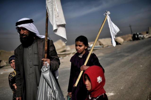 """Iraqis holding white flags walk down a road as they flee Mosul on March 1, 2017, during an offensive by security forces to retake the western parts of the city from Islamic State (IS) group fighters. At least 26,000 people have fled in the 10 days since Iraqi forces launched the push to retake west Mosul, where jihadists put up """"fierce"""" resistance. (Photo by Aris Messinis/AFP Photo)"""
