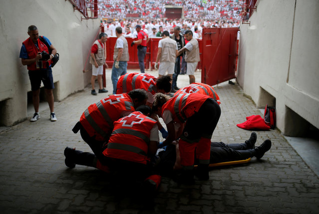 An injured reveller is helped by medical staff during the first running of the bulls at the San Fermin festival in Pamplona, Spain, July 7, 2019. (Photo by Jon Nazca/Reuters)