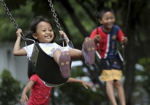 Indonesian children play on swings at a park in Jakarta, Indonesia, Friday, April 4, 2014. (Photo by Tatan Syuflana/AP Photo)