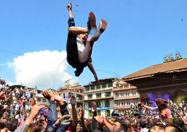 """A reveller is tossed into the air as they celebrate the Holi spring festival in Kathmandu on March 12, 2017. The """"Holi"""" festival of colours is a riotous celebration of the coming of spring and falls on the day after the full moon in early March every year. (Photo by Prakash Mathema/AFP Photo)"""