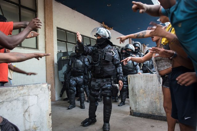 Squatters occupying an abandoned building argue with riot police sent to evict them in Rio de Janeiro, Brazil, on April 11, 2014. (Photo by Yasuyoshi Chiba/AFP Photo)